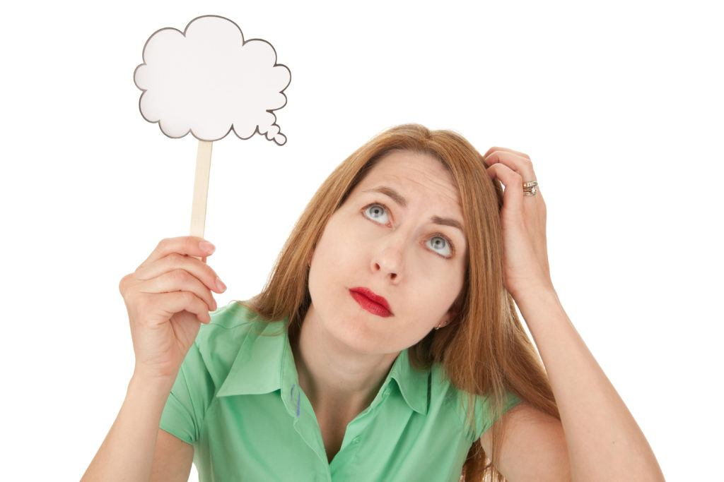 A woman scratching her head and thinking as she holds a blank thought bubble over her head.