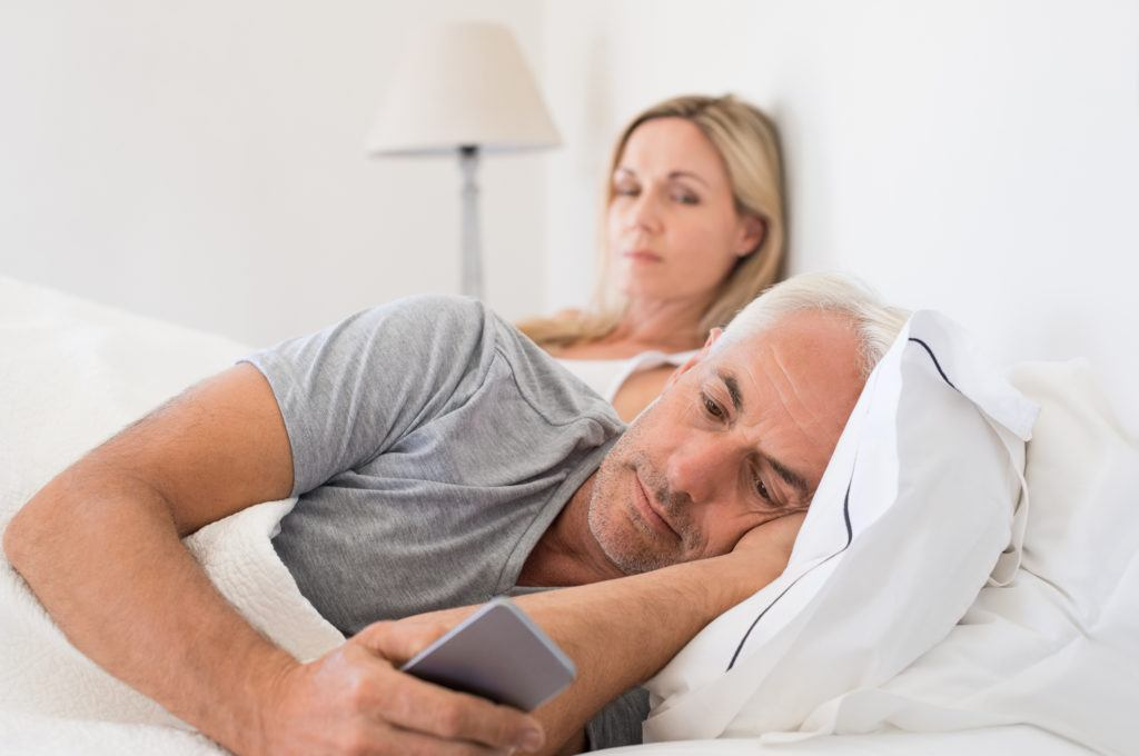 Jealous woman spying her husband mobile phone while he is reading a message. Senior couple in bed while wife is angry as husband using smartphone. Senior husband ignoring wife and texting on smartphone.